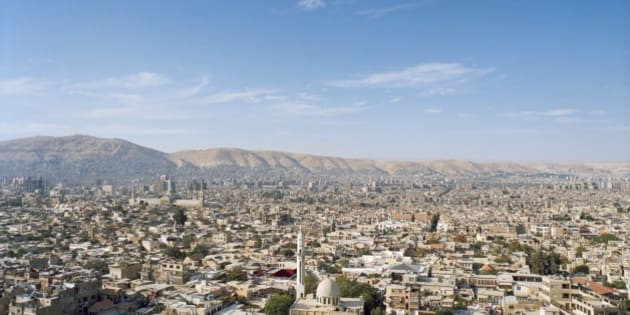 This is a high and wide view of the surrounding neighborhoods of Damascus, Syria. Visible are the rooftops of the homes and businesses of the densely packed city. To the left is the Umayyad Mosque and in the background are the Anti-Lebanon Mountains. Located in southwestern Syria, is not only the country's capital, but a major center for religion, culture, and government.
