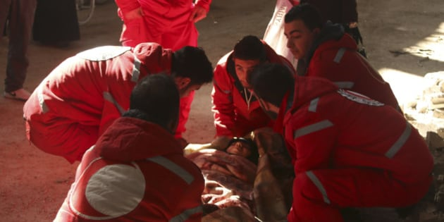 Members of the Syrian Arab Red Crescent help a sick woman in the rebel-controlled area of Aleppo's Bustan al-Qasr, as they head towards the government-controlled area of Aleppo to seek treatment February 1, 2015. REUTERS/Ammar Abdullah (SYRIA - Tags: POLITICS CIVIL UNREST CONFLICT HEALTH)