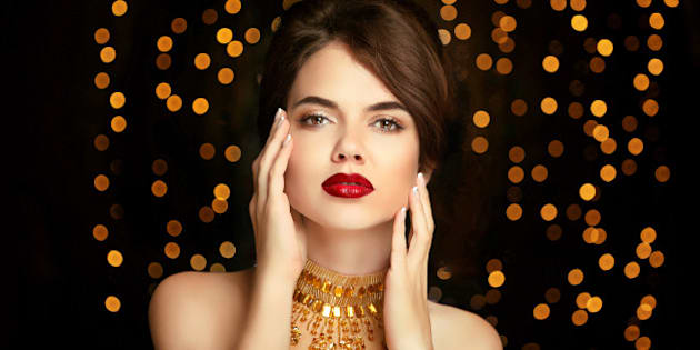 Beauty girl makeup. Fashion jewelry. Elegant lady in golden dress isolated on dark with Christmas party lights background. Vogue style.