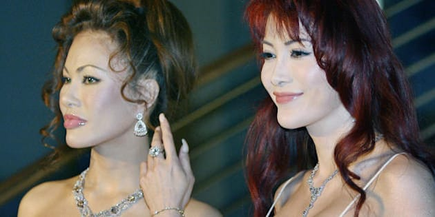 Tokyo, JAPAN:  Japanese sisters Kyoko Kano (L) and Mika Kano (R), pose for photographers upon their arrival at an diamond jewellry collection as part of 'A Celebration of Miracles:Diamonds and Botswana' hosted by the diamond trading company (TDC) in Tokyo, 07 June 2006. Some 10 billion yen (88 million USD) worth and 10,000 carat Diamonds are on display at the collection.  AFP PHOTO/Kazuhiro NOGI  (Photo credit should read KAZUHIRO NOGI/AFP/Getty Images)