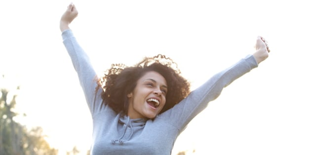 Portrait of a carefree young woman smiling with arms raised