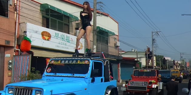 This picture taken on January 3, 2017 shows pole dancers performing on top of jeeps during the funeral procession of former Chiayi City county council speaker Tung Hsiang in Chiayi City, southern Taiwan.