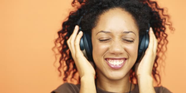Young woman listening to headphones, smiling, close-up