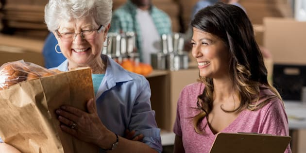 Cheerful Hispanic food bank manager helps a senior Caucasian woman. The older woman is carrying a bag full of groceries.