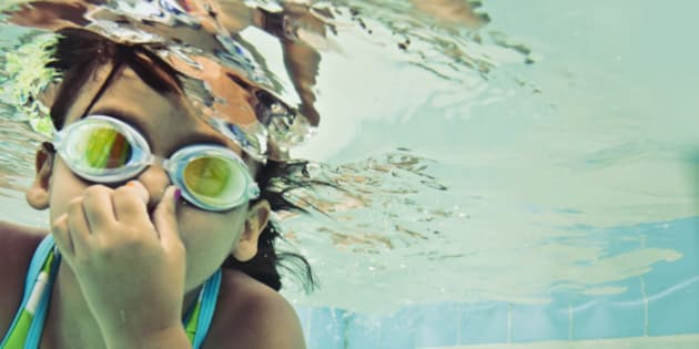 Little girl swimming underwater wearing goggles.