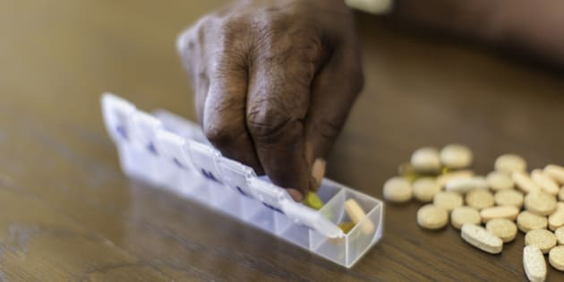 Close up of an african seniors hand placing tablets into a tube. Langebaan, Western Cape, South Africa