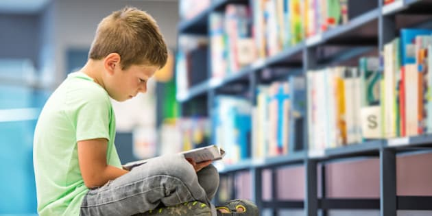 Schoolboy sitting on floor with book in library.