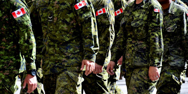 A group of Canadian soldiers wearing green camouflage uniforms march together.