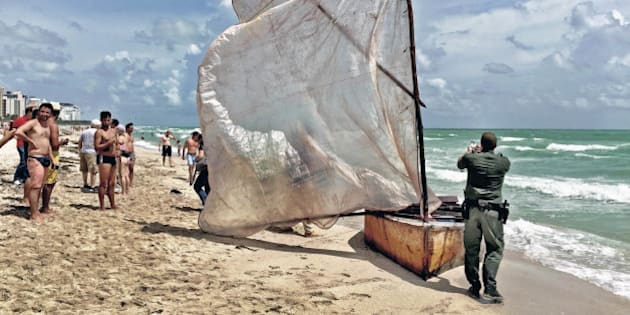 A U.S. Border Patrol agent photographs a boat with a makeshift sail that a group of Cuban migrants used to make landfall on Miami Beach on Tuesday, Sept. 15, 2015. (C.M. Guerrero/El Nuevo Herald/TNS via Getty Images)