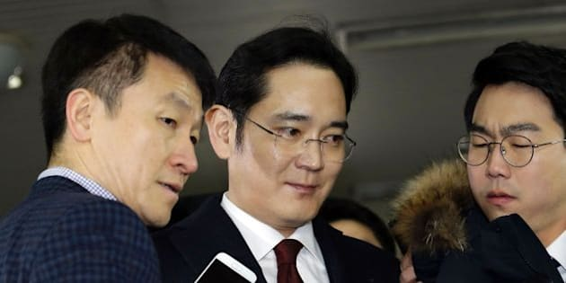 Lee Jae-yong (C) vice chairman of Samsung Electronics, arrives to be questioned as a suspect in a corruption scandal that led to the impeachment of President Park Geun-Hye, at the office of the independent counsel in Seoul on January 12, 2017.   / AFP / POOL / AHN Young-Joon        (Photo credit should read AHN YOUNG-JOON/AFP/Getty Images)