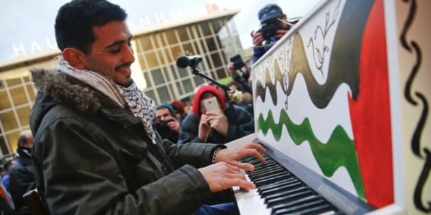 Syrian pianist Aeham Ahmad, winner of Beethoven Prize, plays during a rally outside the main railway station in Cologne, Germany, January 16, 2016, where the vast majority of dozens of New Year Eve assaults on women took place. REUTERS/Wolfgang Rattay
