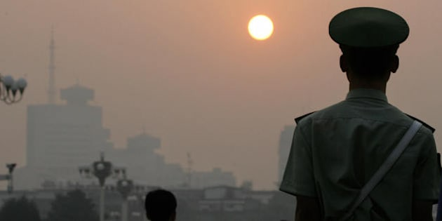 BEIJING, CHINA:  A paramilitary policeman faces the sunrise while patrolling Tiananmen Square on a hazy morning in Beijing, early 09 September 2005.  As Chinese President Hu Jintao started his first visit to North America since becoming the ruling Communist Party's top leader, he is likely to be pressed over China's huge pollution output. China's refusal to cut emissions would set a poor example for developing nations when Kyoto Protocol signatories meet in Montreal in December, Canadian officials said. AFP PHOTO/Frederic J. BROWN  (Photo credit should read FREDERIC J. BROWN/AFP/Getty Images)