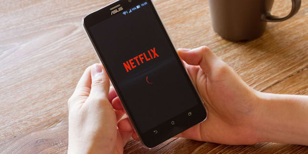 Chiang Mai, Thailand - April 26, 2016: man hand holding screen shot of Netflix application showing on Asus Zenfone 2 mobile phone. Netflix is a global provider of streaming movies and TV series.