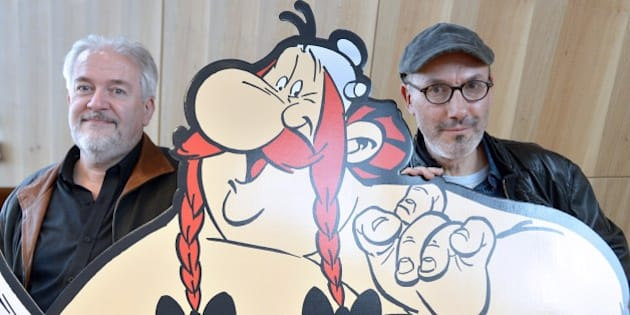 French cartoonist Didier Conrad (L), and the coauthor of the popular comic book Asterix with French cartoonist and author Albert Uderzo (unseen) writer and designer Jean-Yves Ferri pose beside a cardboard cut-out of Asterix and Obelix characters during a press conference in Paris on October 12, 2015 for the release of the new Asterix album 'Le Papyrus de Cesar' (Caesar's Papyrus). The 36th book in the Asterix series 'Le Papyrus de Cesar' (entitled in English : Asterix and the Missing Scroll), will be released in France on October 22, 2015. AFP PHOTO / BERTRAND GUAY        (Photo credit should read BERTRAND GUAY/AFP/Getty Images)
