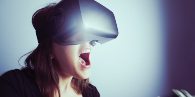 A mid-adult woman wearing a virtual reality headset,  using a video game controller, totally involved in a video game. Mouth open, shouting with excitement; close-up, wide-angle image.
