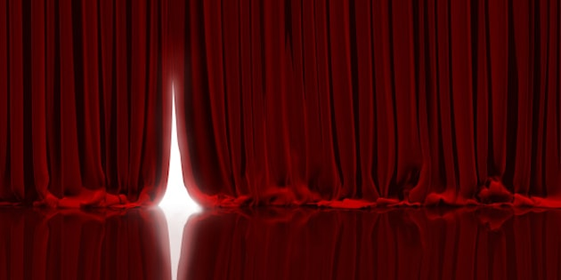 Opening red curtain on theater or cinema stage.