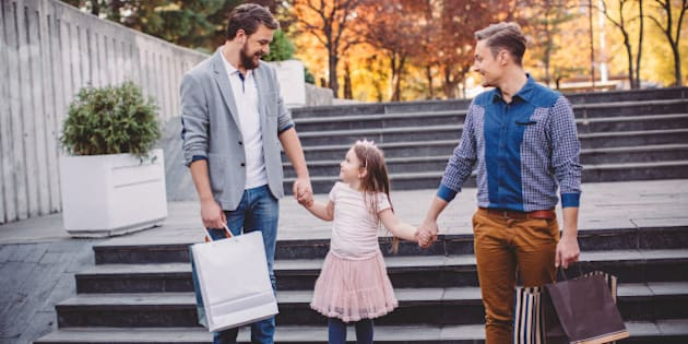 Young gay parents with their daughter walking from the shopping mall. They are happy and joyful. Caucasian ethnicity. Sunny autumn day.