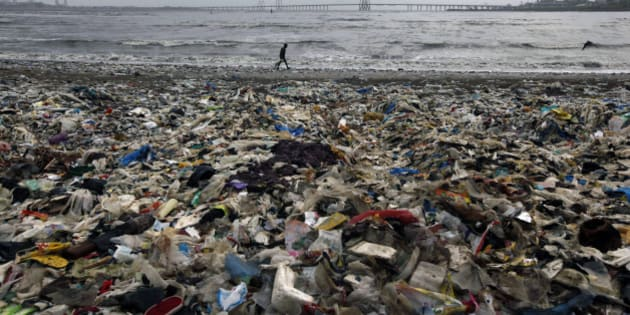 A man walks by the Arabian Sea coast piled with garbage, mostly plastic waste, in Mumbai, India, Monday, July 30, 2012. (AP Photo/ Rajanish Kakade)