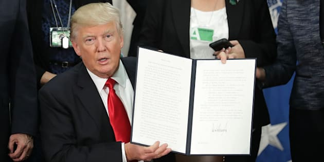 U.S. President Donald Trump, center, holds up a signed executive order at the Department of Homeland Security (DHS) in Washington, D.C. U.S., on Wednesday, Jan. 25, 2017. Trump acted on two of the most fundamental -- and controversial -- elements of his presidential campaign, building a wall on the border with Mexico and greatly tightening restrictions on who can enter the U.S. Photographer: Chip Somodevilla/Pool via Bloomberg