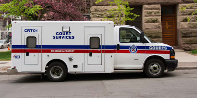 TORONTO, ONTARIO, CANADA - 2015/05/13: Toronto Court Services van.  The white van has the words 'Court Services' in the center in blue, along with the word 'Courts' in white on a blue stripe that sits over a red one.  The truck is in front of a brown stone building and some flowering trees. (Photo by Roberto Machado Noa/LightRocket via Getty Images)