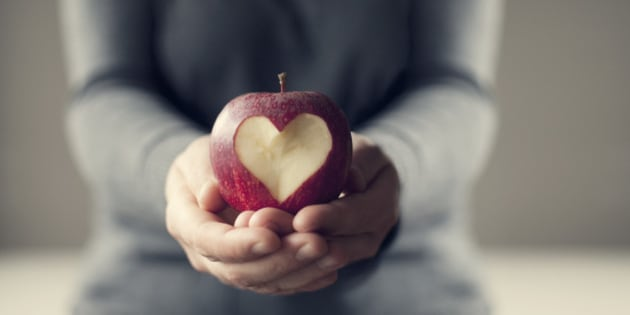 A person holding a red apple in their hands.There is a heart carved out of the apple.