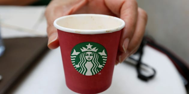 A woman displays a red Starbucks cup at a Starbucks cafe in Beirut, Lebanon November 20, 2016. Picture taken November 20, 2016. REUTERS/Jamal Saidi