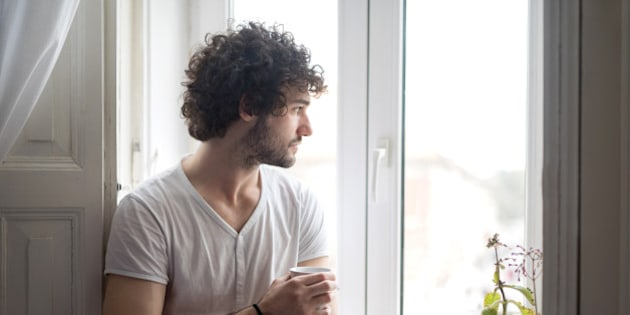 Young serious man at home thinking while holding cup of coffee and looking through the window