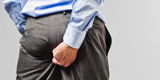 Rude businessman scratches his buttocks - NOT something to do in public!