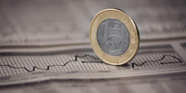 Brazilian currency over the Newspaper with graphic. Economia brasileira com moeda em close de 1 Real sobre grA!fico.