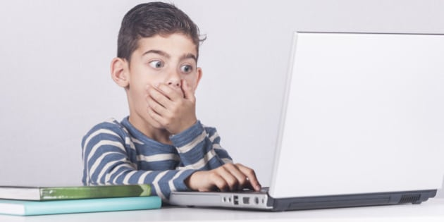 Young boy reacts while using a laptop. Internet safety for kids concept. Toned image with selective focus