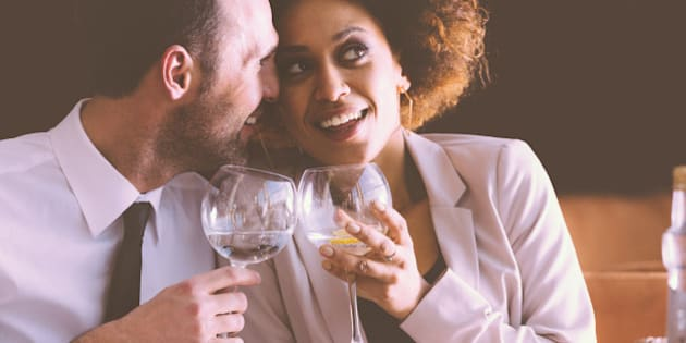 Happy couple - afro american woman and caucasian man in elegant outfits having lunch or dinner in restaurant, sitting at the table and holding wine glasses. Man embracing her girlfriend.