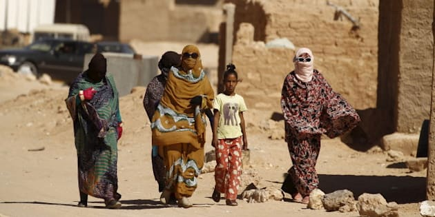 """Indigenous Sahrawi women walk through Al Smara desert refugee camp in Tindouf, southern Algeria March 4, 2016. In refugee camps near the town of Tindouf in arid southern Algeria, conditions are hard for indigenous Sahrawi residents. Residents use car batteries for electricity at night and depend on humanitarian aid to get by. The five camps near Tindouf are home to an estimated 165,000 Sahrawi refugees from the disputed region of Western Sahara, according to the United Nations refugee agency UNHCR. REUTERS/Zohra Bensemra SEARCH """"THE WIDER IMAGE"""" FOR ALL STORIES  Matching text ALGERIA-SAHARA/"""