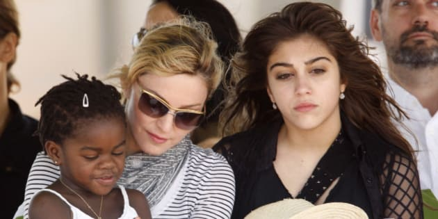 Pop star Madonna sits with her adopted Malawian child Mercy James and daughter Lourdes during a bricklaying ceremony at the site of her Raising Malawi Girls Academy, near the capital Lilongwe, April 6, 2010.   REUTERS/Mike Hutchings (MALAWI - Tags: ENTERTAINMENT)
