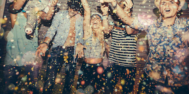 Teenagers enjoying confetti in front of roller door whilst partying in street