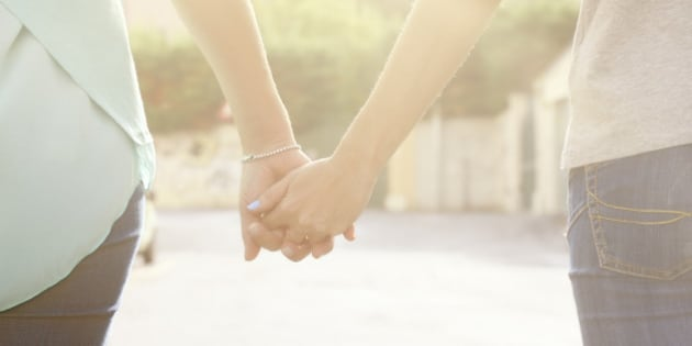 Lesbian Holding Hands and Walking in a street. Rear view.