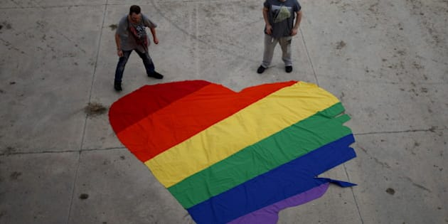 Fer Franco, 25, (R) and his partner Rafa Varon, 23, stand next to a heart-shaped cloth with rainbow colors as they pose for a photo, to mark Gay Pride day, in downtown Malaga, southern Spain, June 28, 2015. The heart-shaped cloth with rainbow colors is the logo of the Andalusian Federation of Lesbian, Gay, Bisexual, Transgender and Intersex (LGBTI) Arco Iris, which Franco and Varon are volunteers of.  REUTERS/Jon Nazca