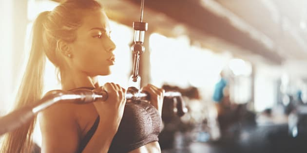 Closeup side view of an attractive brunette working out at a gym. She's using lat pull down machine with a reverse grip, the exercise that hits back muscles and arms. She's wearing tiny black sports top.Toned shot.