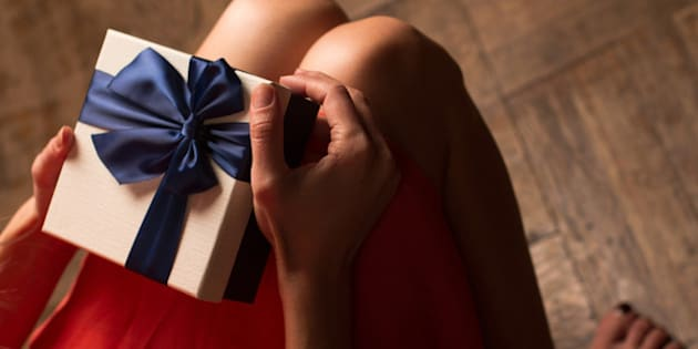 Top view woman with red dress holding a gift box with blue ribbon on her knees