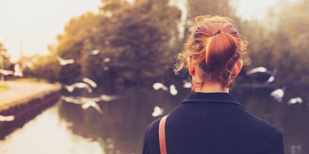 Rear view of a young redhead woman dressed in black looking at birds by a river
