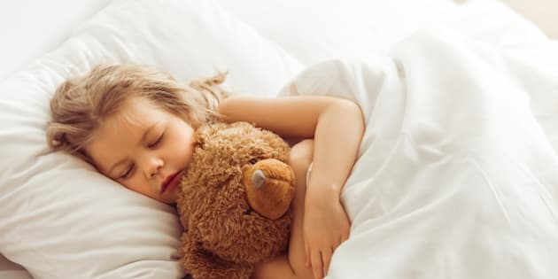 Sweet little girl is hugging a teddy bear while sleeping in her bed at home