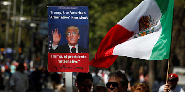 A man holds up a placard with an image of U.S. President Donald Trump during a march to protest against Trump's proposed border wall and to call for unity, in Mexico City, Mexico, February 12, 2017. REUTERS/Jose Luis Gonzalez