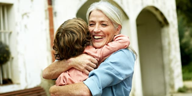 Happy grandmother looking away while embracing grandson in yard