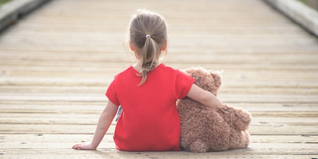 Little girl in a red dress waiting on a boardwalk hugging teddybear, view from behind