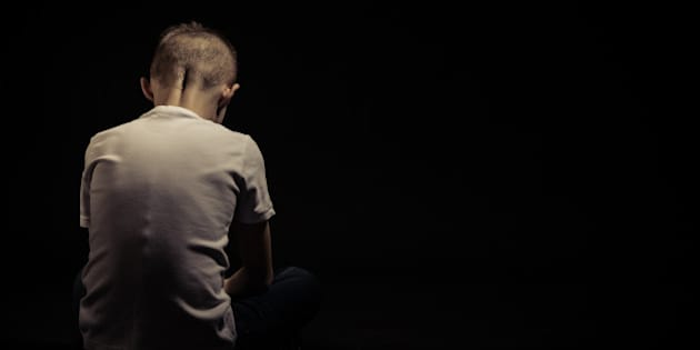 Rear View of a Sad Silhouette Young Boy Sitting on the Floor Against Black Background with Copy Space.
