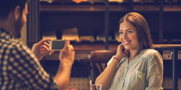 Young happy woman enjoying in a cafe while her boyfriend is photographing her with cell phone.