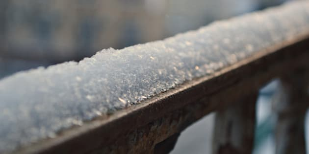 A snow cap on a metal railing of a balcony