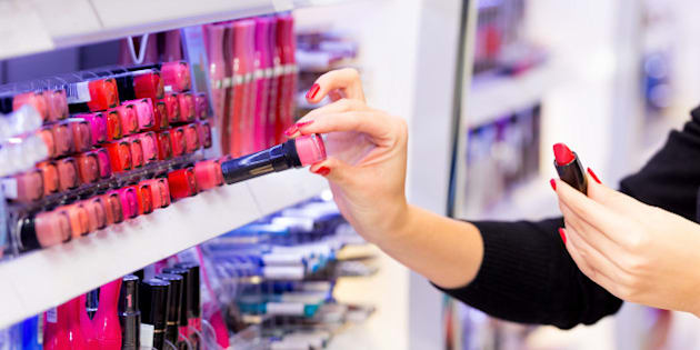 Woman shopping for red lipstick at department store