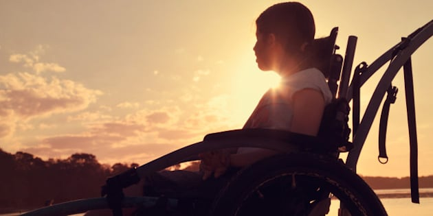 Teenage girl with cerebral palsy sits in a wheel chair watching the sunset by a river.