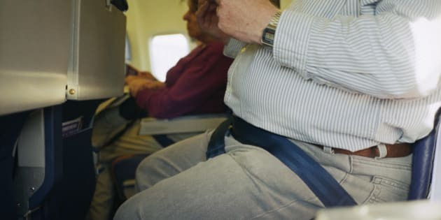A close up of an overweight man's stomach on a plane.