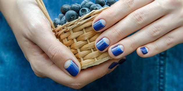 Female Hand With Blue Nail Design Holding A Small Basket Berries